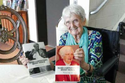 Marj Carpenter is pictured at one of her book signings at the Heritage Museum, holding up both of her Ridin' Fence books, which are available at Heritage Museum. Marj Carpenter was an author, a well–known, respected, trusted and adored journalist and a friend to many.